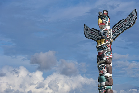 the totem pole: isolated totem wood pole in the blue cloudy background Stock Photo