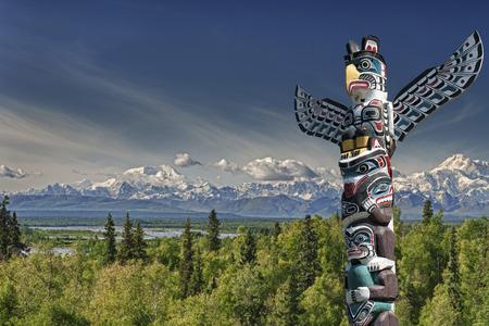 totem indien: Isolé poteau en bois de totem fond bleu de montagne Banque d'images