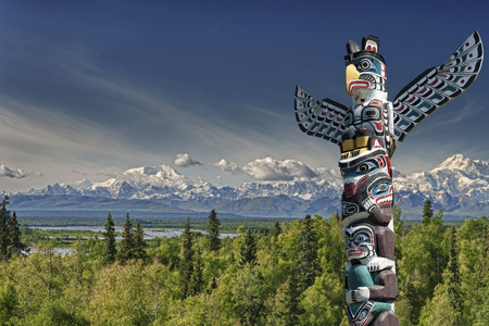canadian pacific: Isolated totem wood pole in mountain blue background Stock Photo