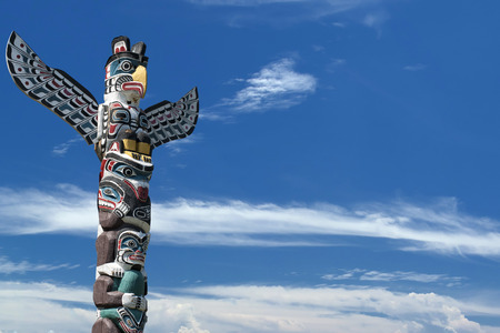 northwest indian art: isolated totem wood pole in the blue cloudy background Stock Photo