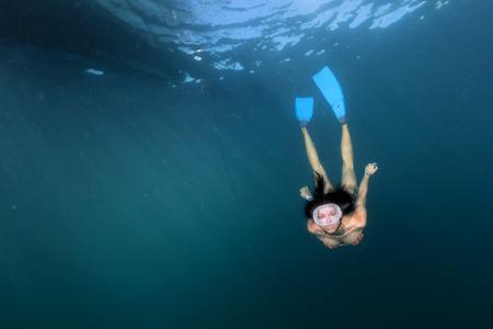 girl underwater: zeeleeuw zegel komt naar zwart haar duiker meisje onderwater Stockfoto