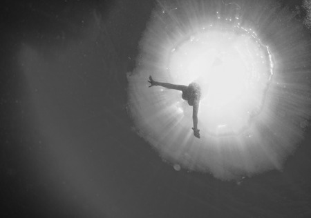 submerge: backlight diver underwater coming to the deep ocean Stock Photo