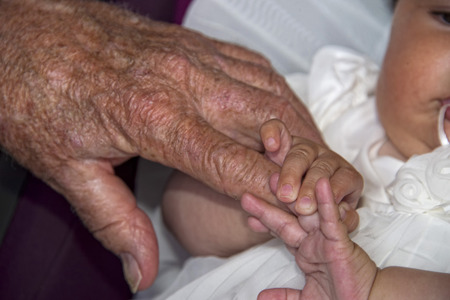 infant hand: old retired man hand while holding newborn infant hand Stock Photo