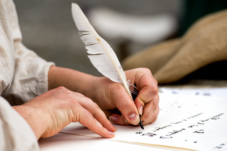 hands while writing a letter with a plume