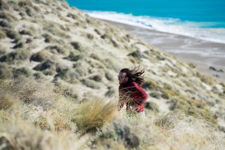 long hair man: happy long hair man running on the cliffs by the sea