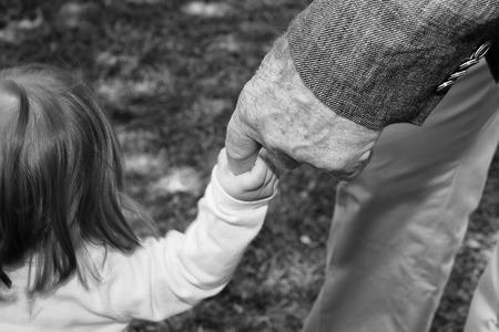 bebes recien nacidos: anciano mano mientras sostiene reci�n nacido en blanco y negro Foto de archivo