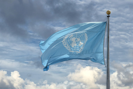 NEW YORK - USA - 11 JUNE 2015 Waving united nations UN flag in the deep blue sky background Imagens - 42008435