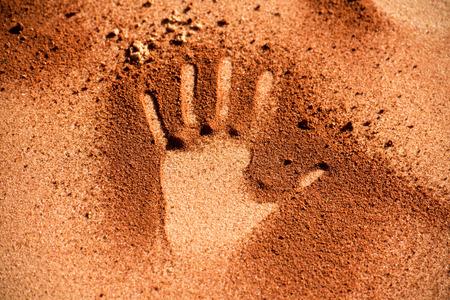 sandy soil: Red australian soil hand shape on sandy beach Stock Photo