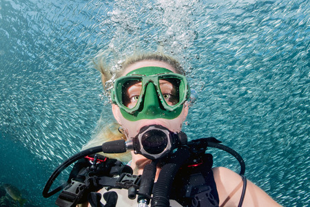 scuba: beautiful diver blonde girl diving in the deep blue sea Stock Photo