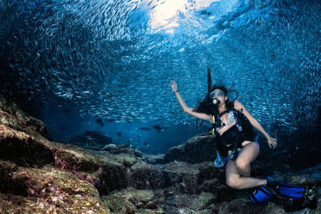 sea fishing: Black hair young and pretty mexican latina Scuba diver while going Inside a giant sardines school of fish bait ball in the reef and blue sea