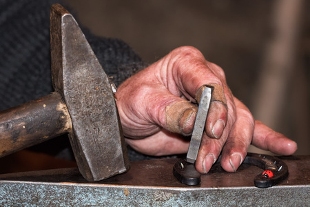 wicker work: old retired man hand detail while working iron Stock Photo