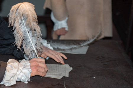 scribe: hands while writing a letter with a plume