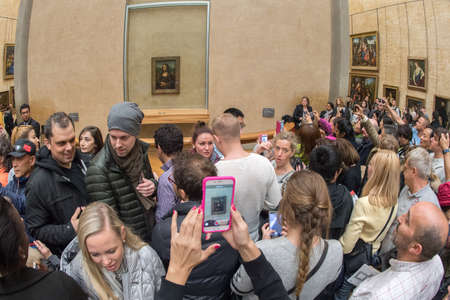 mona lisa: PARIS, FRANCE - APRIL 30, 2016 - lot of people inside louvre museum, taking pictures of Mona Lisa painting
