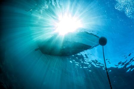 la cadena del ancla del barco bajo el agua con los rayos del sol