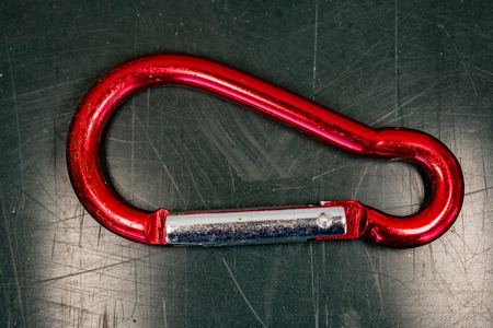 karabiner: Red rusted used old karabiner close up detail isolated on green