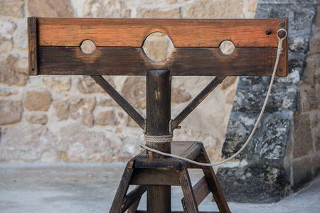 ancient prison: Old wooden pillory close up on castle stone wall background