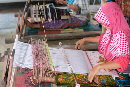 woman hand working at loom in Indonesia