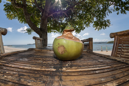 fresh coconut on bamboo table on the beach in tropical island paradise resort