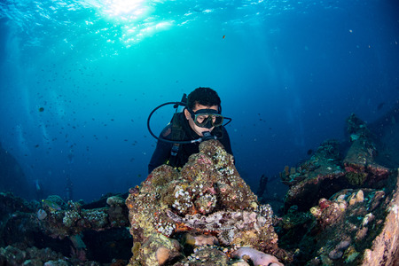 Scuba diver underwater portrait in the deep blue ocean and backlight sun