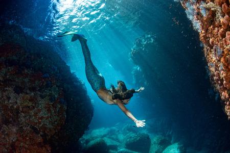 cola mujer: pelo negro de la sirena bajo el agua nadando en el mar azul profundo y que le mira Foto de archivo