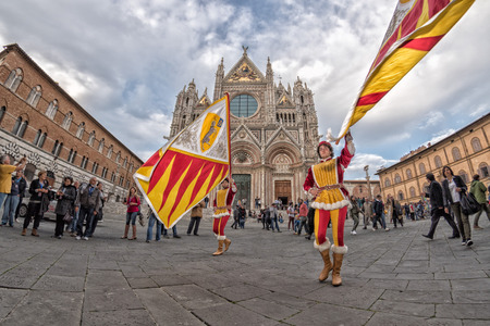 SIENA, ITALY - MARCH 25 2017 - Traditional flag wavers parade. 17 district of medieval town on parade in dome place preparing for worldwide famous horse race called Palio