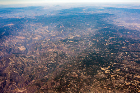 farmed fields and mountains near mexico city aerial view landscape from airplane leon city guadalajara