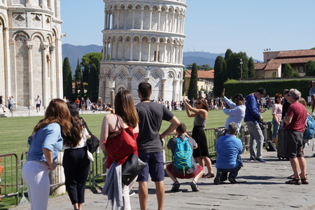 PISA, ITALY - SEPTEMBER 26 2017 - Tourist taking pictures while pushing and holding famous leaning tower in piazza dei miracoli 新闻类图片