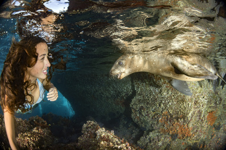 black hair Mermaid swimming underwater in the deep blue sea with a sea lion