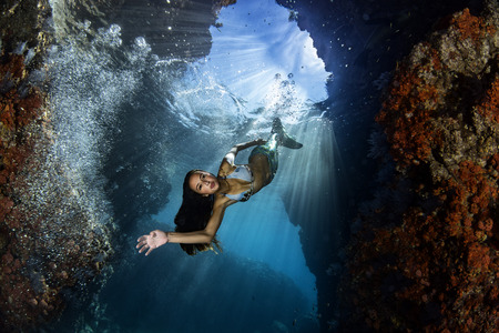 black hair Mermaid swimming underwater in the deep blue sea and looking at you
