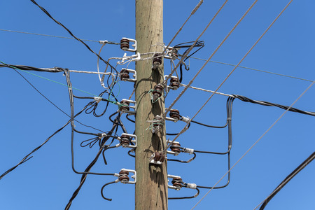 Electric cables tangle on old wood post