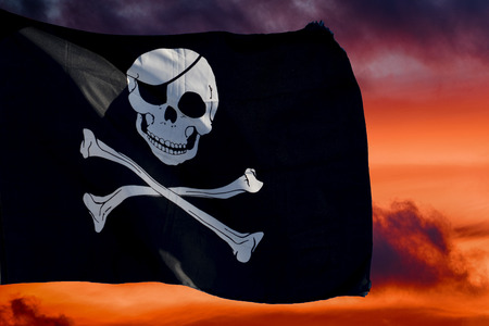 waving pirate flag jolly roger on sky background Stockfoto