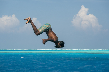 Young maldives man diving from boat in turquoise crystal waters