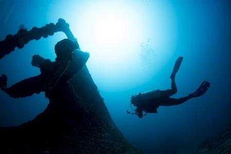 Elica del relitto della nave sott'acqua con la sagoma del subacqueo durante l'immersione Archivio Fotografico