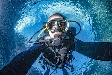 Scuba diver underwater selfie in the deep blue ocean and backlight sun and sardines bait ball