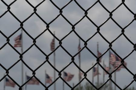 Waving usa flags behind metallic fence grid