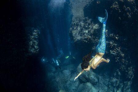 black hair Mermaid swimming underwater in the deep blue ocean