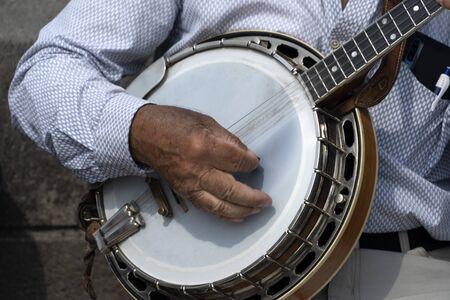 street artist playing banjo musician detail of hands close up