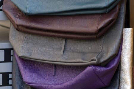 different colors leather woman bags on display at the market