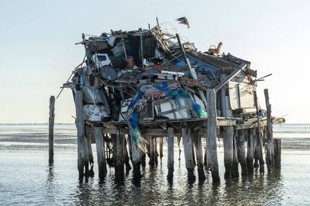 Stilt house full of plastic and rubbish on the sea Imagens