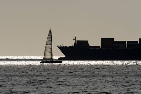 sail boat and big container ship silhouette at sunset