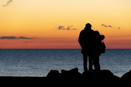 lovers hugging in front of the sea at sunset landscape