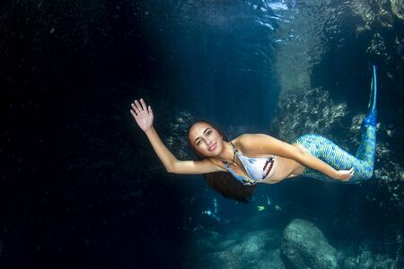 beutiful Mermaid swimming underwater in the deep blue sea and looking at you with scuba divers