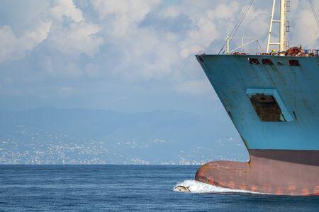 dolphin jumping near big ship bow Stock Photo