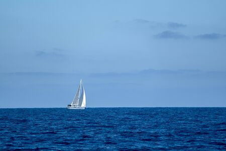 small sailboat on deep blue sea and sky background Stockfoto - 150085126