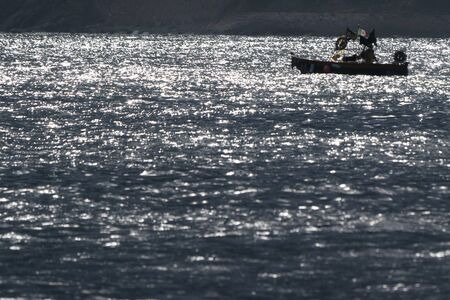 fishing boat silhouette at sunset in mediterranean sea