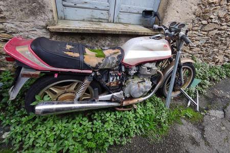 abandoned motorbike with moss on saddle