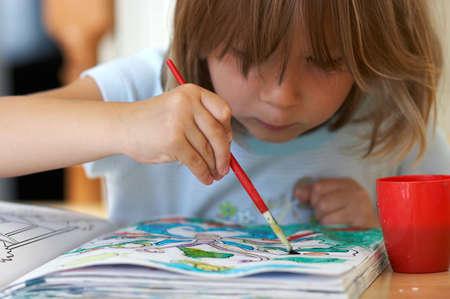 Pretty girl coloring a book Standard-Bild