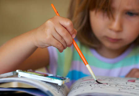 Girl coloring a book Standard-Bild
