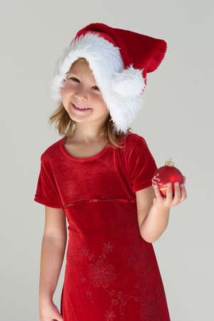 Little girl in red dress with red christmas ball