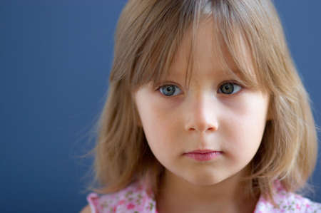 Portrait of serious little girl over blue background photo